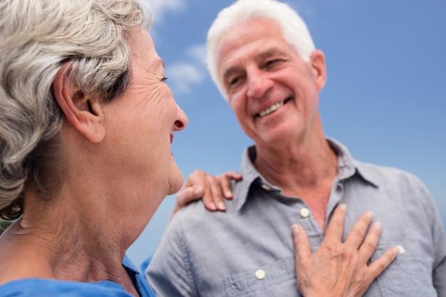 ビーチでお互いを受け入れて年配のカップル