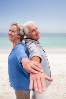 腕を広げて背中合わせに立っている年配のカップル