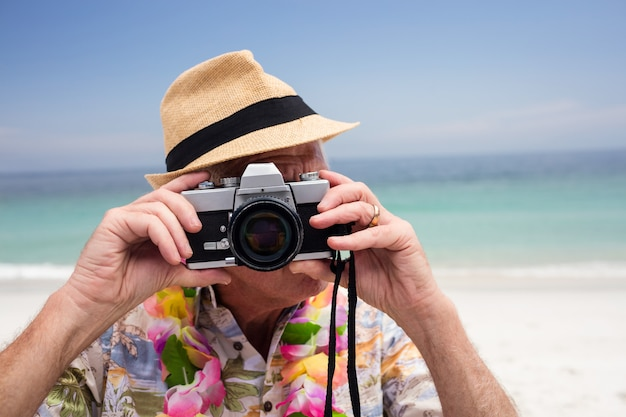 年配の男性がカメラで写真を撮る