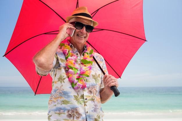 Старший мужчина держит зонтик во время разговора по телефону
