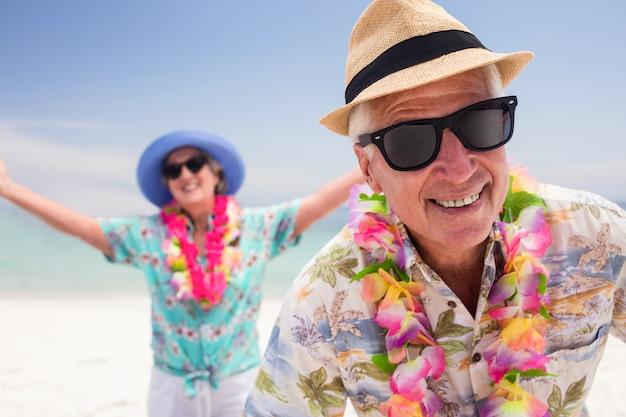ビーチで一緒に楽しんで幸せな先輩カップル