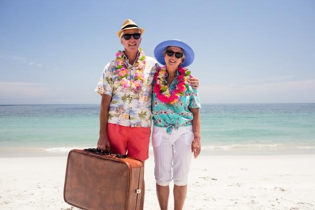 ビーチでスーツケースを持って幸せな先輩カップル