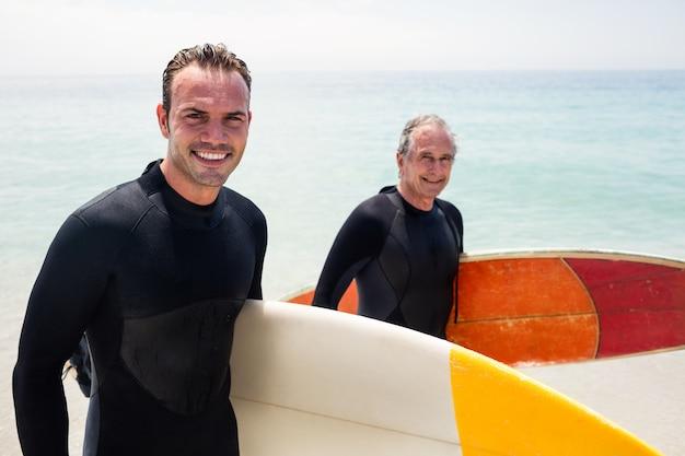 幸せな父とサーフボードを保持しているウェットスーツの息子の肖像画