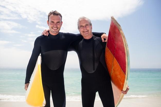 幸せな父と息子のビーチで抱きしめるウェットスーツの肖像画