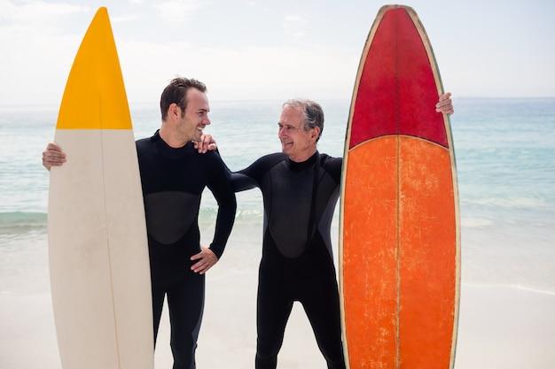 父と息子のビーチに立っているサーフボードと
