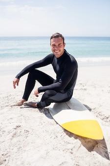 Счастливый серфер в гидрокостюм, сидя с доской для серфинга на пляже