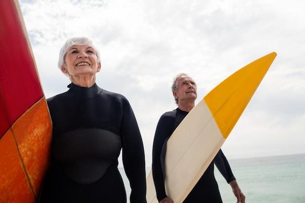 ビーチでサーフボードを保持しているウェットスーツの年配のカップル