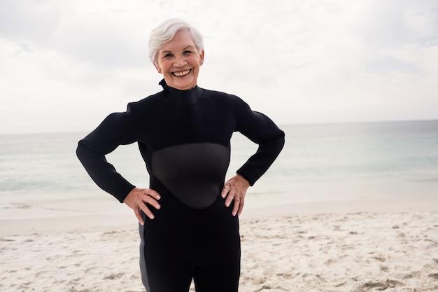 ビーチに立っているウェットスーツで幸せな年配の女性