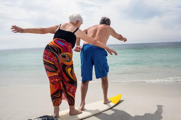 年配のカップルがビーチでサーフィン