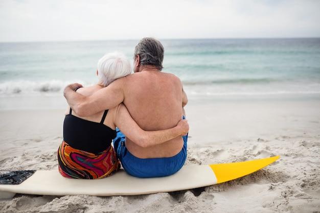 ビーチでサーフボードの上に座って年配のカップル