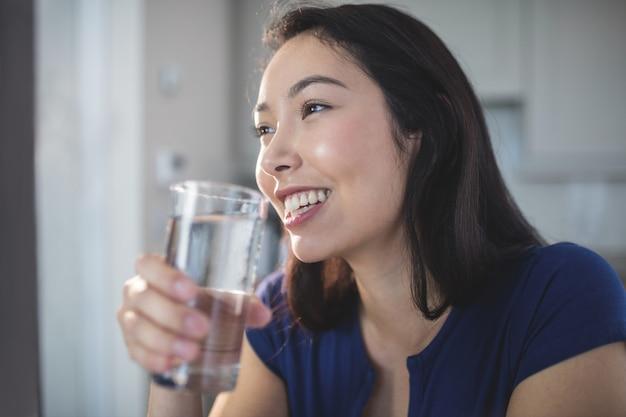 キッチンで水のガラスを飲む若い女性