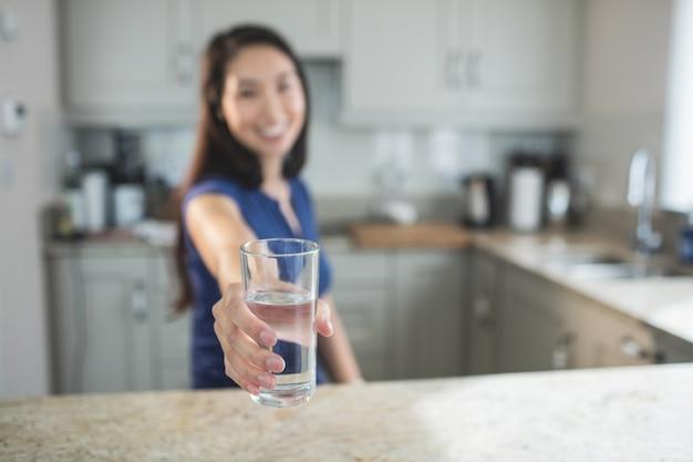 キッチンで水のガラスを保持している若い女性