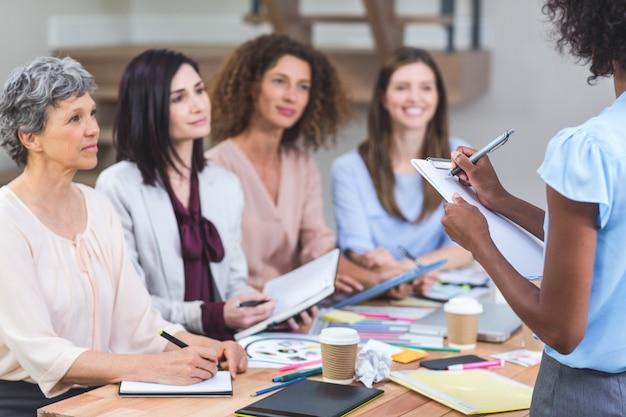 Женщина отмечает в буфер обмена, а коллеги слушают презентацию