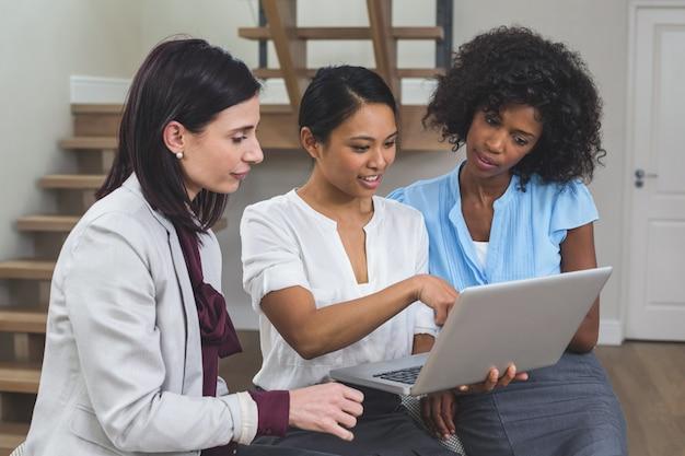 ラップトップで議論する女性ビジネス部門の同僚