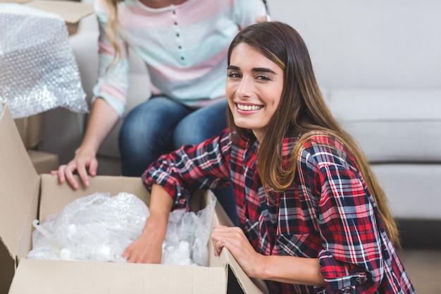 Женщина распаковывает картонные коробки