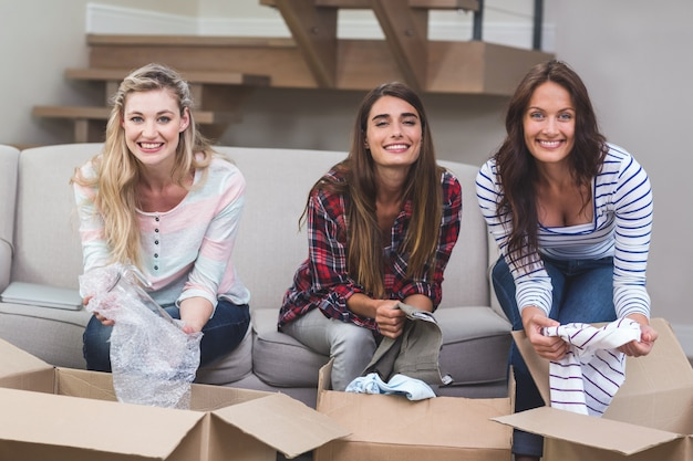 Друзья распаковывают картонные коробки