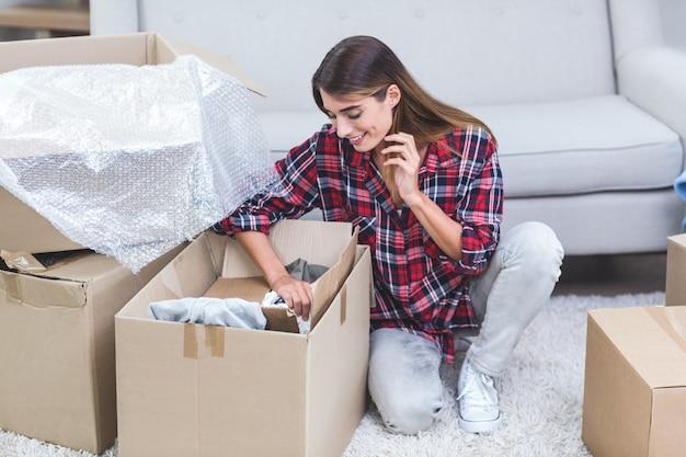 Красивая женщина распаковывает картонные коробки