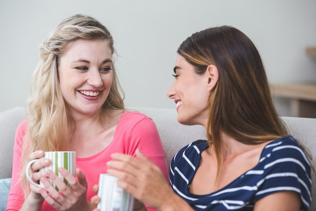 Две красивые женщины держат чашку кофе и разговаривают в гостиной
