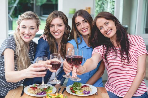 お友達と食事をしながら赤ワインのグラスを保持