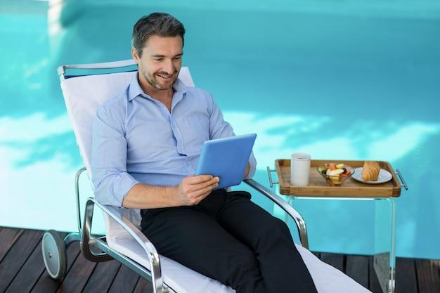 プールの近くのデジタルタブレットを使用してスマートな男