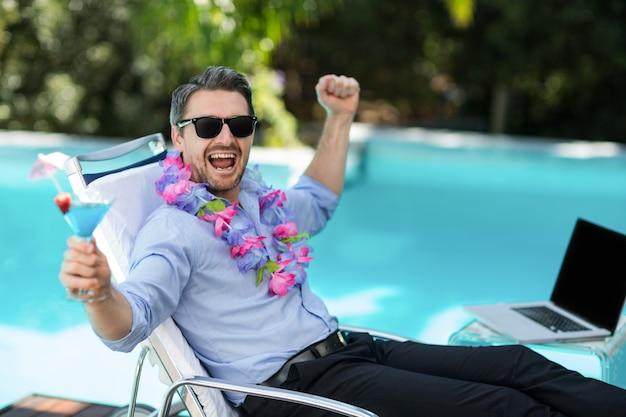 興奮した男の花輪を着て、マティーニグラスを保持