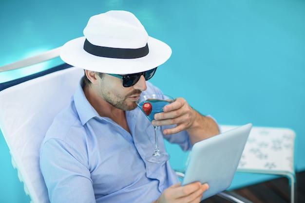 プールの近くのデジタルタブレットを使用しながらマティーニを持つスマートな男