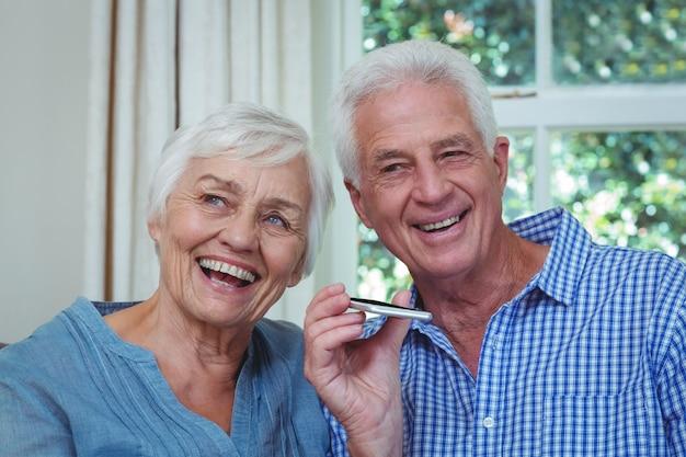 年配のカップルが電話で音楽を聴く