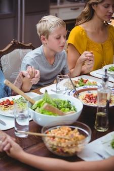 ダイニングテーブルで祈りながら手を繋いでいる家族