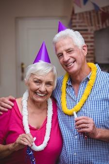 パーティーホーンを保持している笑顔の年配のカップルの肖像画