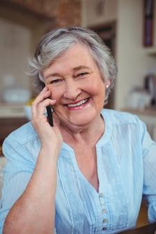 Портрет старшей женщины разговаривает по мобильному телефону