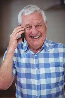 Улыбающийся старший мужчина разговаривает по телефону
