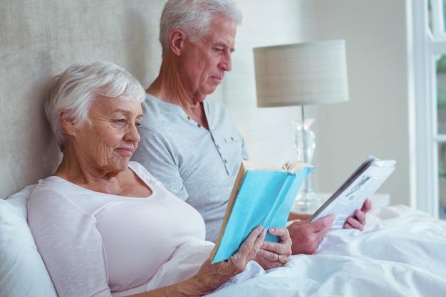 Пожилая пара читает книгу на кровати