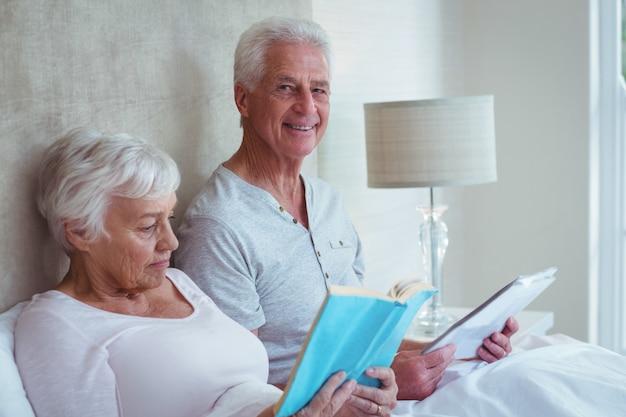 Счастливый старший мужчина с женой, чтение книги в спальне