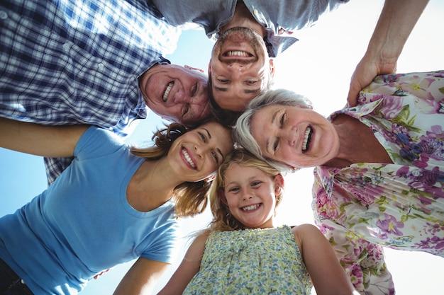 空に対してハドルを形成する陽気な家族