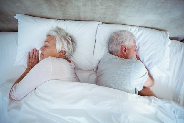 ベッドで寝ている年配のカップル