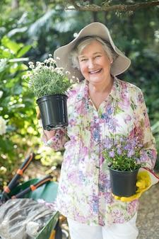 鉢植えの植物を保持している年配の女性の肖像画