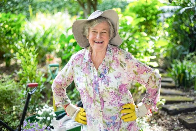 庭に立っている幸せの年配の女性