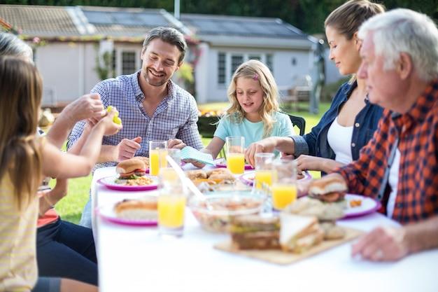 Счастливая многопоколенная семья ест за столом