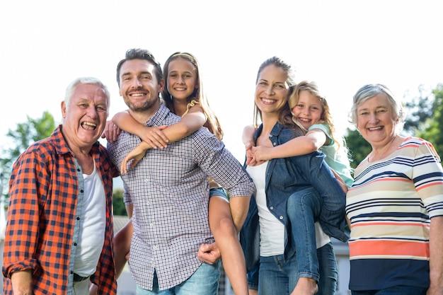 裏庭で祖父母と女の子を運ぶ幸せな親