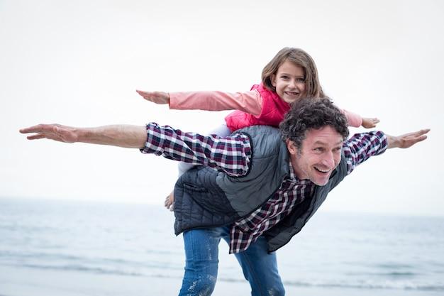 Счастливый отец, перевозящих дочь на спине на берегу моря