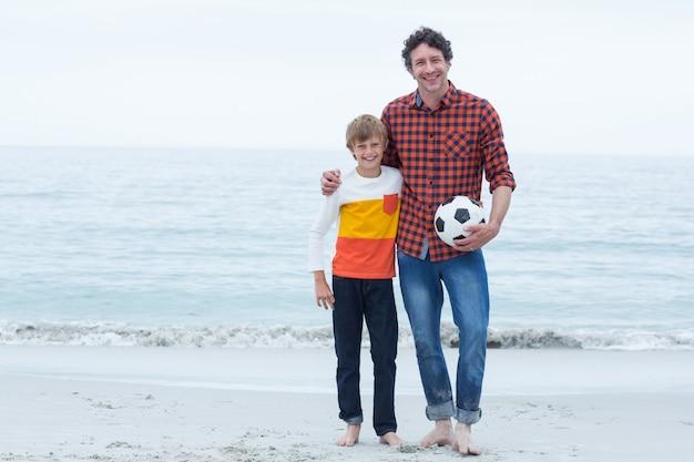 Отец и сын, держа футбольный мяч на берегу моря