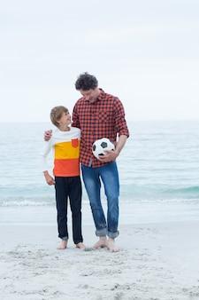 Отец и сын с футбольным мячом на берегу моря