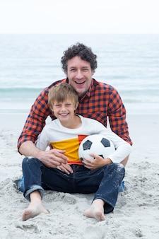 Отец и сын, держа футбольный мяч, сидя на пляже