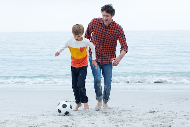 Отец и сын играют в футбол на пляже