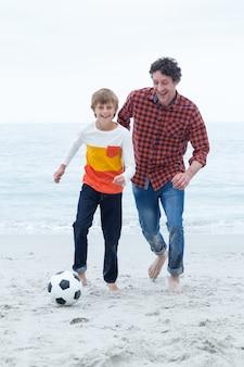 Веселый отец и сын играют на берегу моря