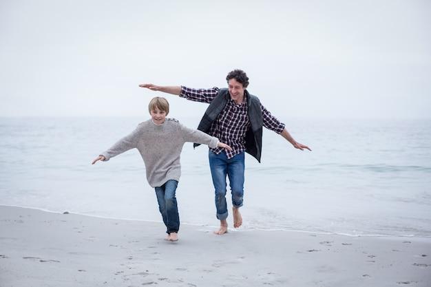 父と息子の両腕でビーチを走る