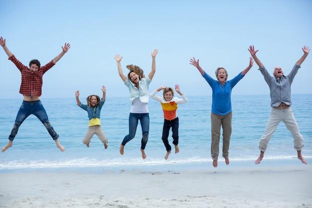 Семья нескольких поколений прыгает на берегу моря