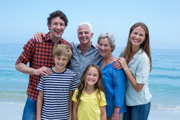 Веселая многопоколенная семья стоит на берегу моря