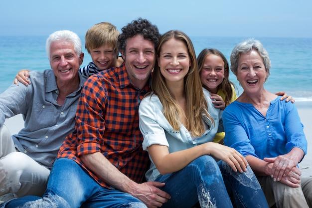 Веселая многопоколенная семья отдыхает на пляже