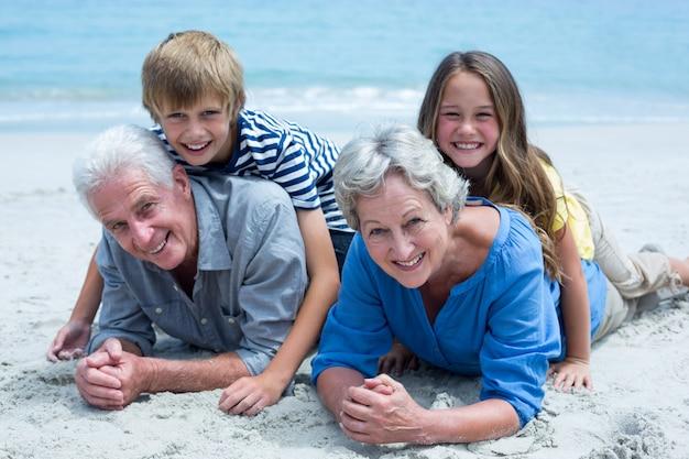 Дети лежат на бабушке и дедушке на берегу моря